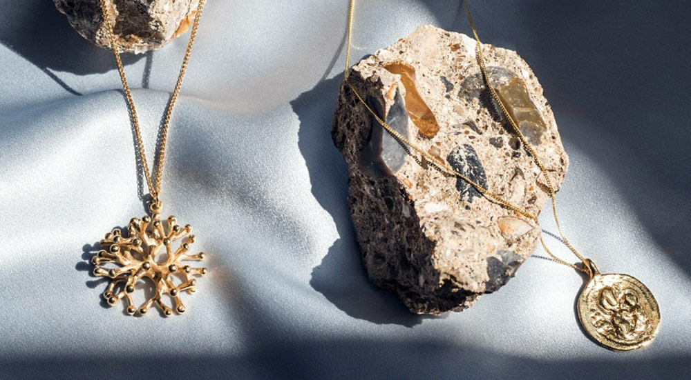 Two gold necklaces on a silk sheet with stones shaped by the sea