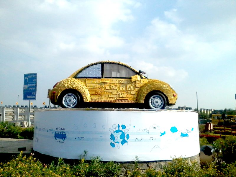 A bright yellow Volkswagen beetle made of scrap material