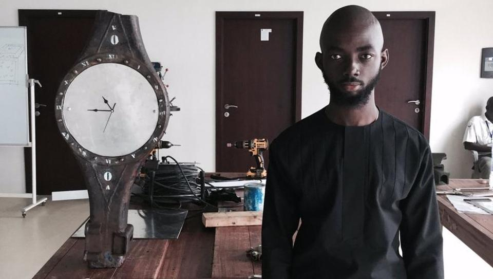 Joseph stands next to his clock made from ewaste